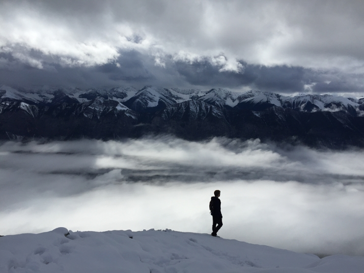 Man walking alone through a black-white-gray landscape with mountains and clouds.